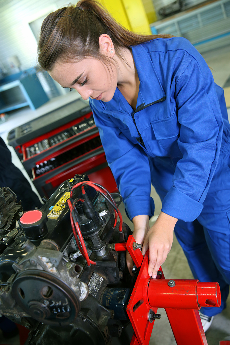 Student girl working in auto repairshop